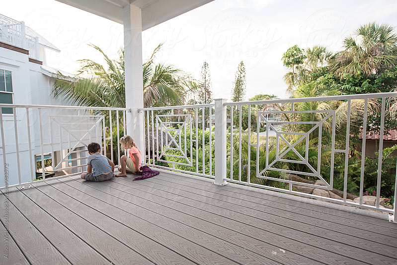 Two Children Talking On A Porch by Alison Winterroth for Stocksy United