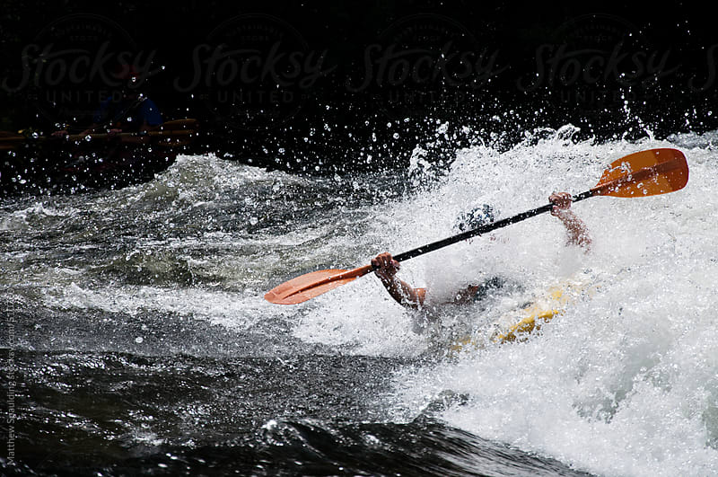 Kayaker with paddle surfing in wild whitewater river wave by Matthew Spaulding for Stocksy United