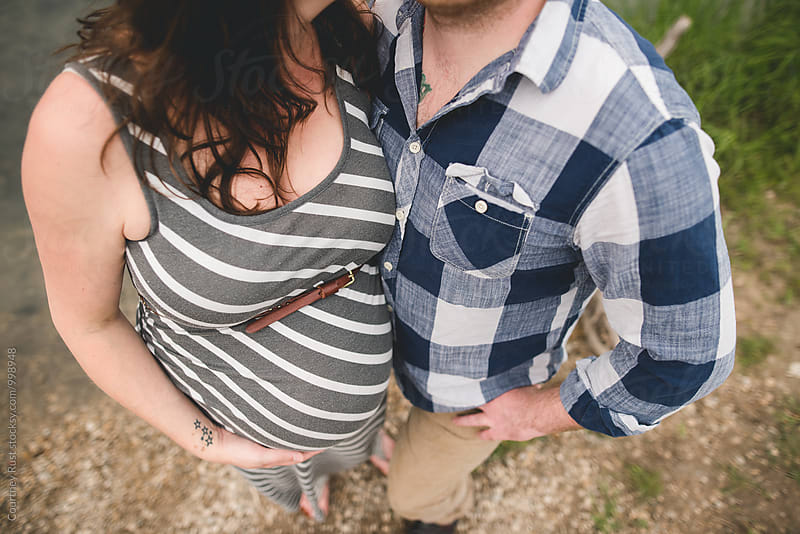 Portrait looking down at pregnant couple by Courtney Rust for Stocksy United