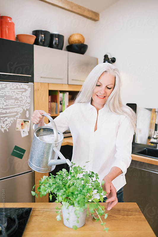 Senior woman watering a plant. by Lilly Bloom for Stocksy United