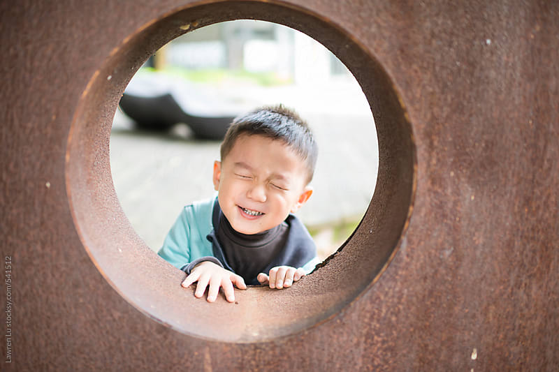 Boy Looking Through Circular Architectural Design Feature in Wall by Lawren Lu for Stocksy United
