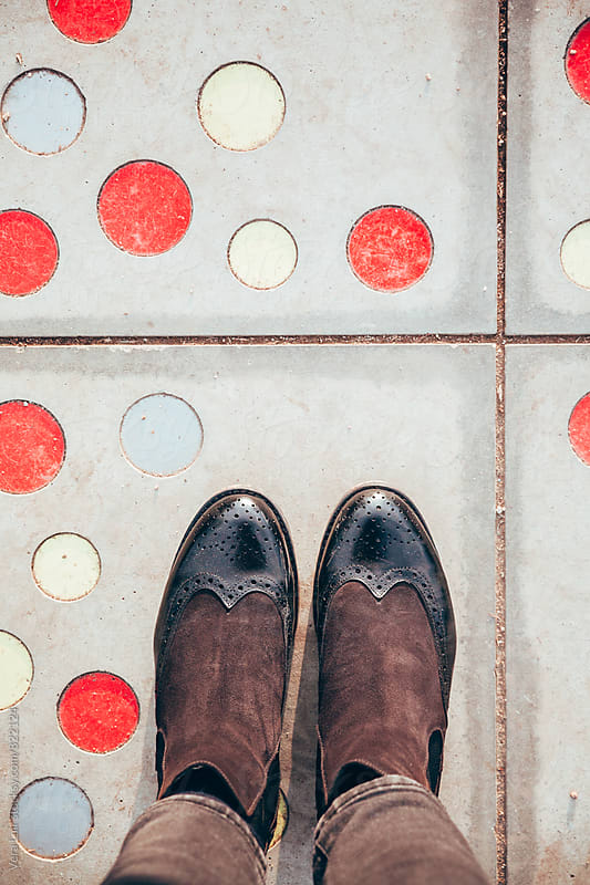 Woman feet, on colored dots floor by Vera Lair for Stocksy United