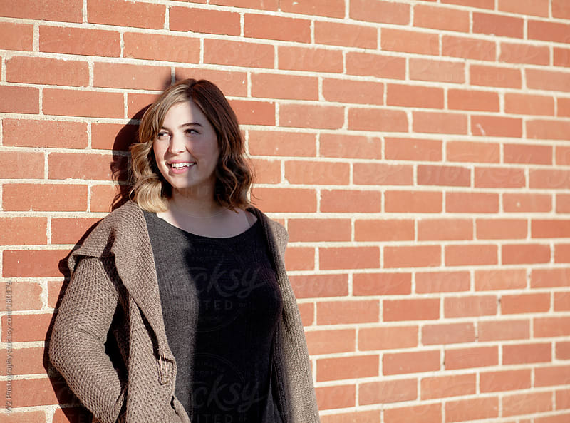 Portrait of a smiling young woman, against brick wall by W2 Photography for Stocksy United