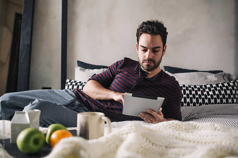 Man Using a Tablet in Bed in the Morning by Lumina for Stocksy United
