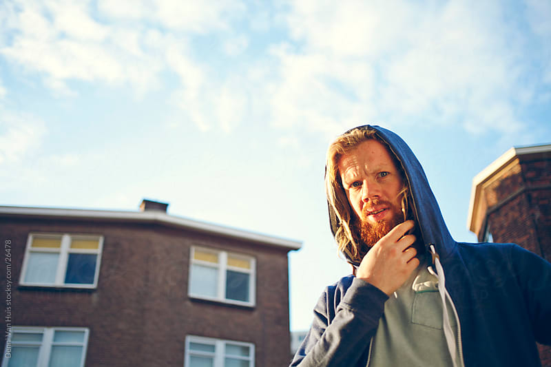 Young bearded ginger man wearing a hoody on a street by Denni Van Huis for Stocksy United