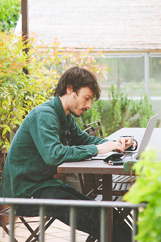Young creative designer working with laptop on table. Outdoors. by BONNINSTUDIO for Stocksy United