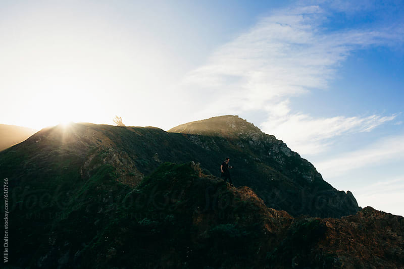 A Man Hiking Down a Cliff during Sunrise by Willie Dalton for Stocksy United