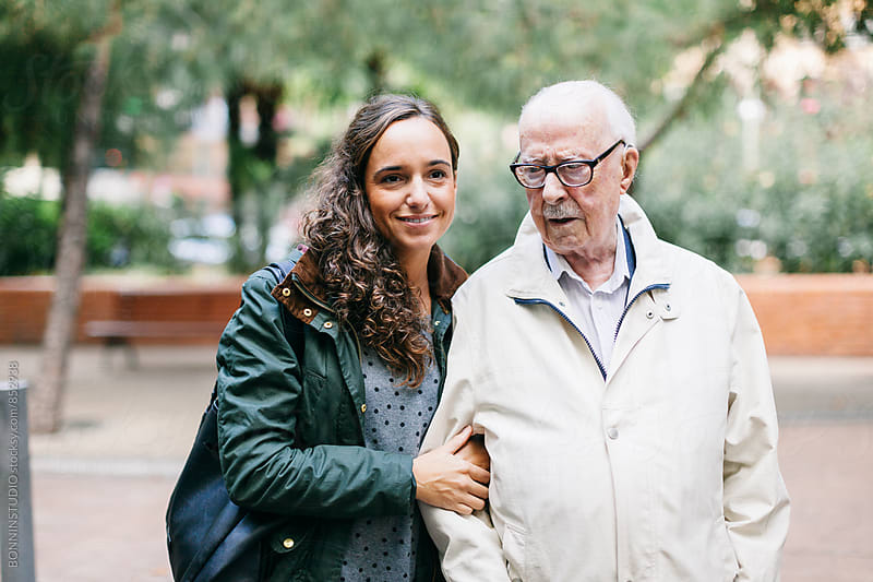Grandpa and his granddaughter walking in a park. by BONNINSTUDIO for Stocksy United