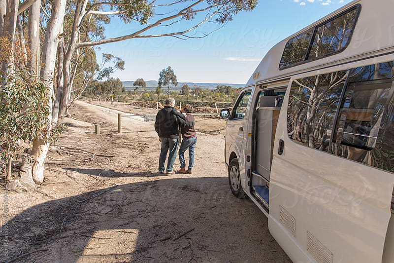Grey nomad couple standing in front of parked campervan by Ben Ryan for Stocksy United