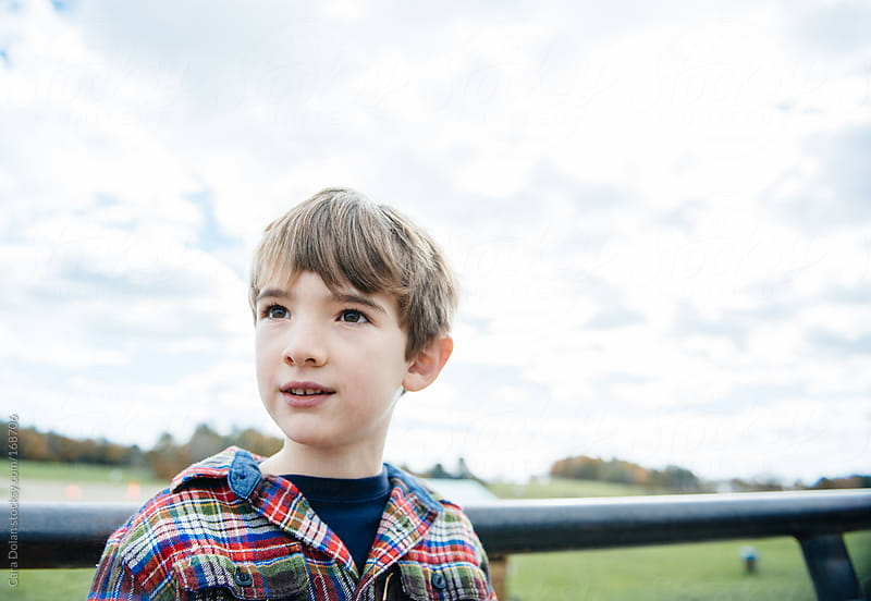 Boy looks across a pasture in autumn by Cara Dolan for Stocksy United