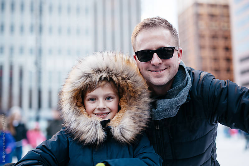 father and son outdoors in the city in winter by Kelly Knox for Stocksy United