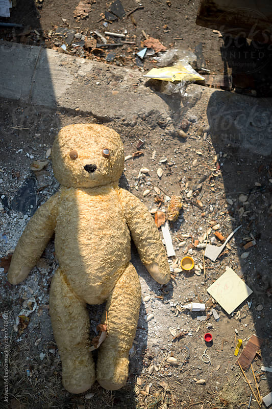 Broken teddy bear next to a dumpster by Jovana Milanko for Stocksy United