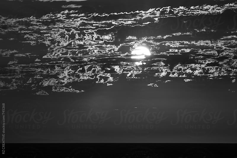 Black and white moon rise over the sea. by RZ CREATIVE for Stocksy United