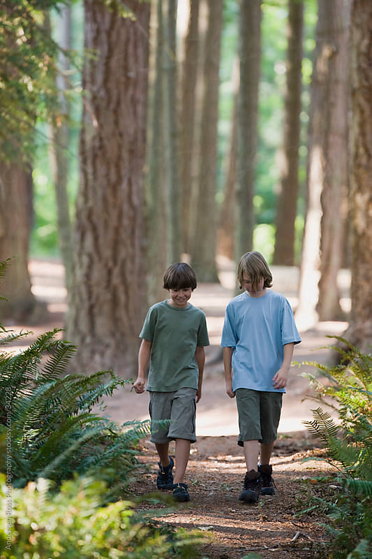 Two boys (10-11) walking through forest by Andersen Ross Photography for Stocksy United