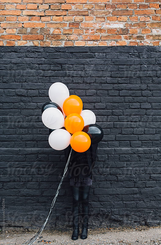 Girl in a Witch Costume Holding Balloons by Lumina for Stocksy United