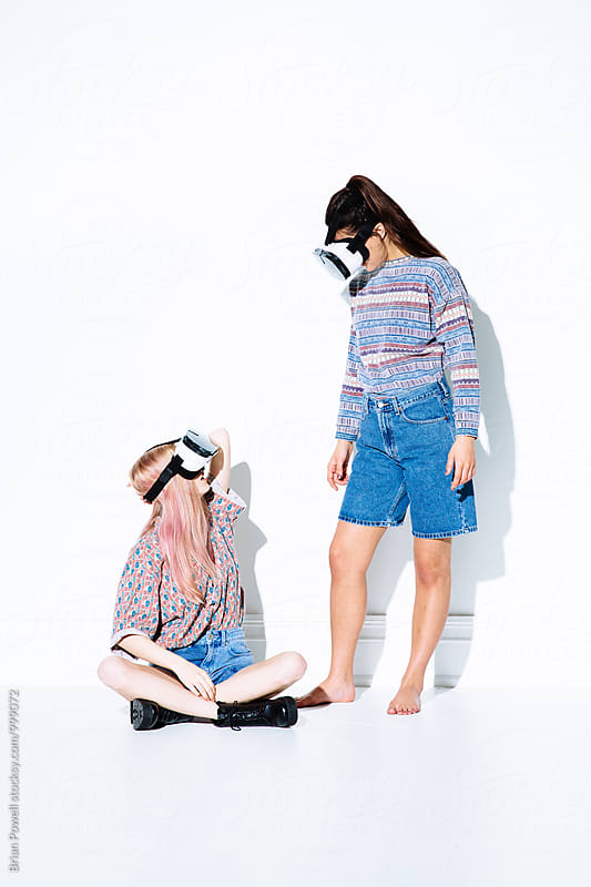 two friends trying virtual reality headsets by Brian Powell for Stocksy United