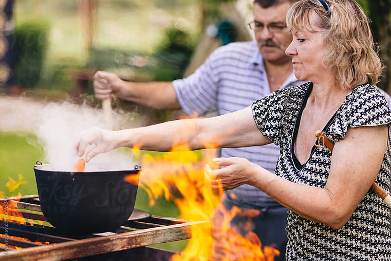 Mature man and woman preparing food on bbq by Ilya for Stocksy United