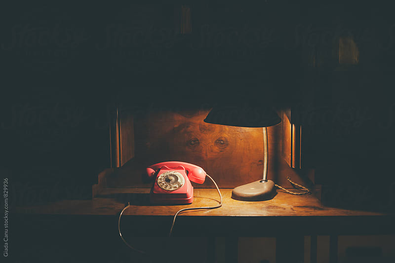 Vintage phone on a wooden desk by Giada Canu for Stocksy United