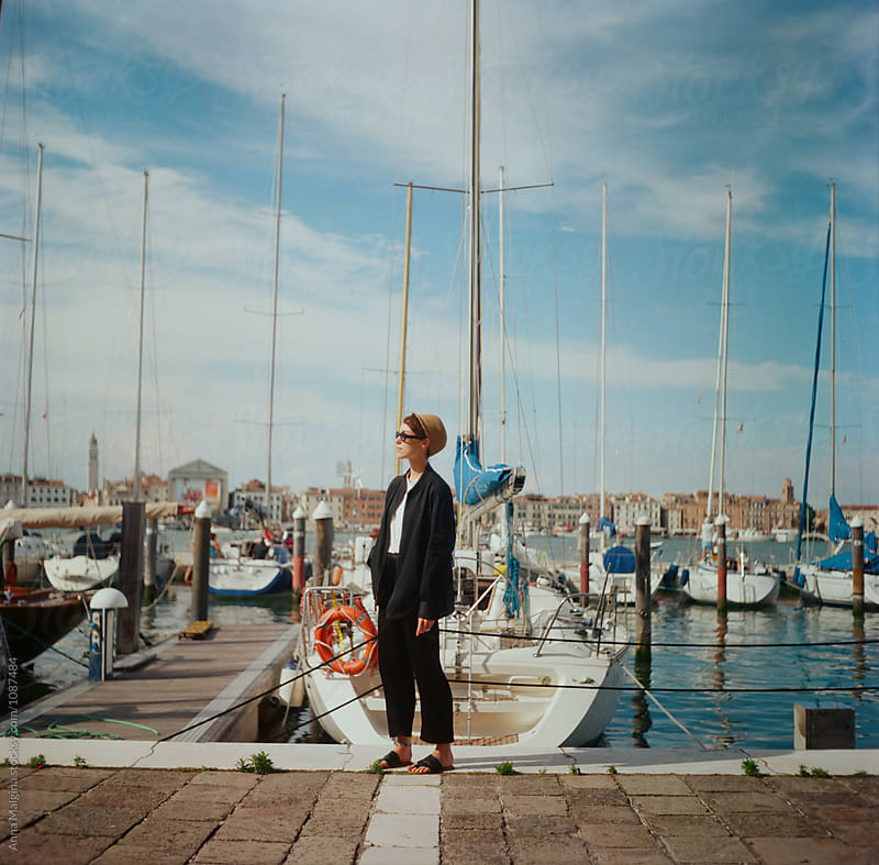 A portrait of a young beautiful woman in front of a boats by Anna Malgina for Stocksy United
