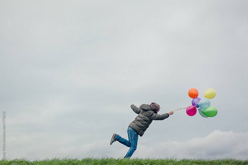Boy running after balloons on a cloudy windy day by Cindy Prins for Stocksy United