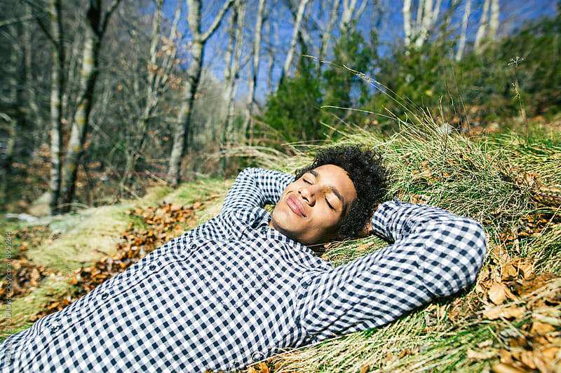 Man enjoying a sunny day lying on grass. by BONNINSTUDIO for Stocksy United