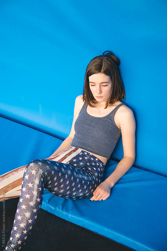 Sad young woman on trampoline by Danil Nevsky for Stocksy United