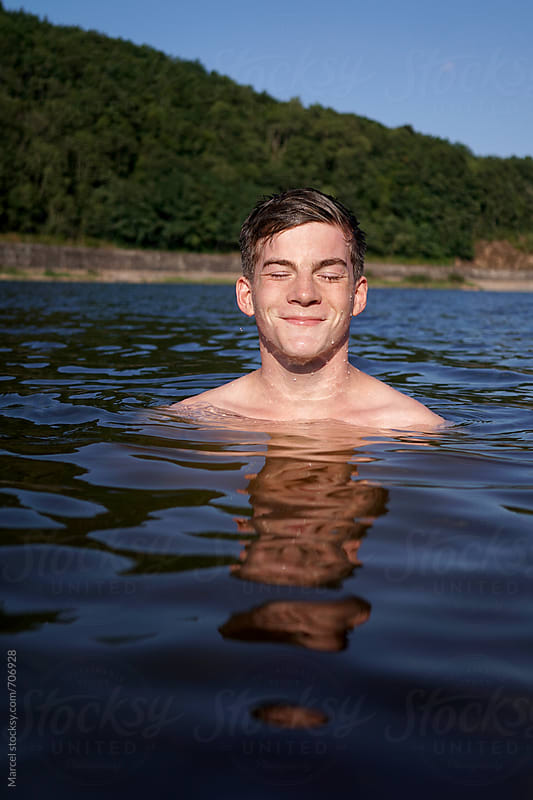 Young male in a lake by Marcel for Stocksy United
