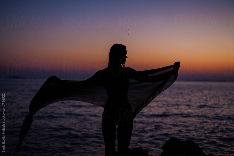 Shadow of a fit girl in the sunset holding a pareo by Sanja (Lydia) Kulušić for Stocksy United