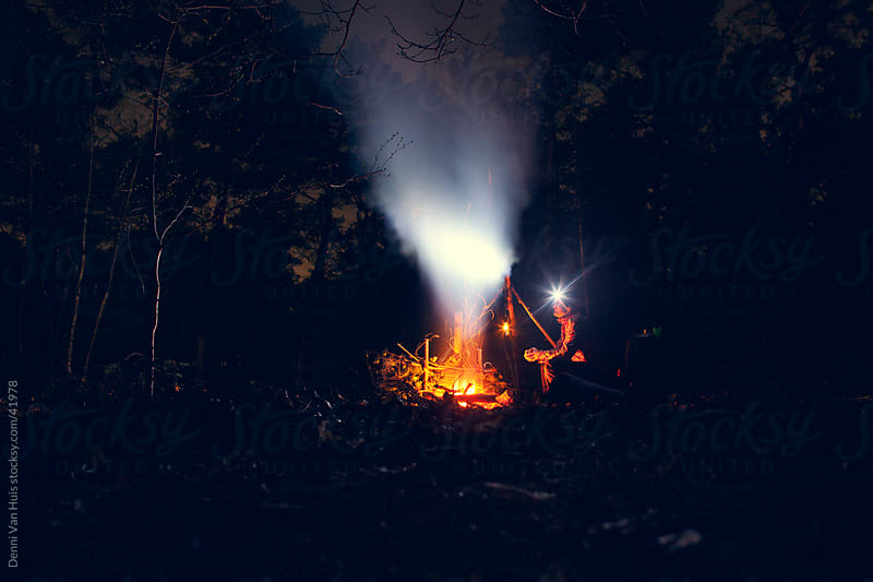 Someone sitting next to a camp fire at night by Denni Van Huis for Stocksy United