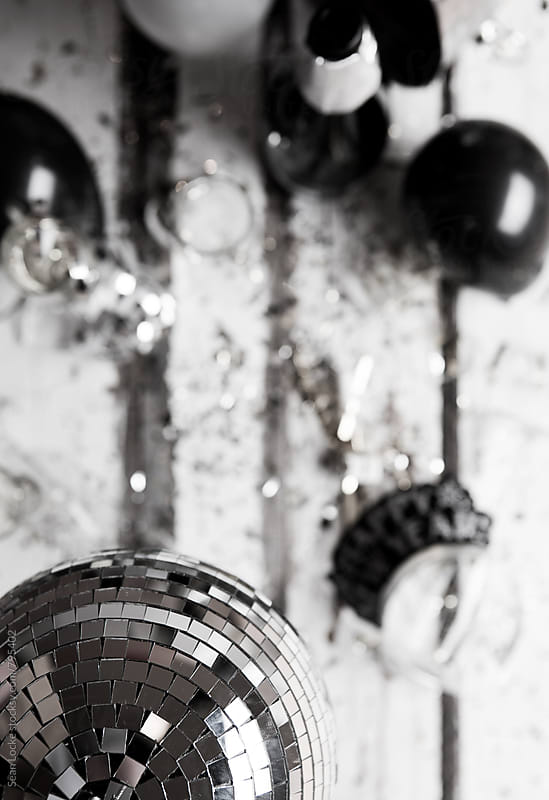 NYE: Focus On Mirrored Ball Over Messy Party Table by Sean Locke for Stocksy United