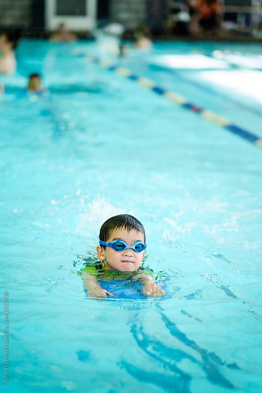 Asian boy swimming in the pool by Suprijono Suharjoto for Stocksy United