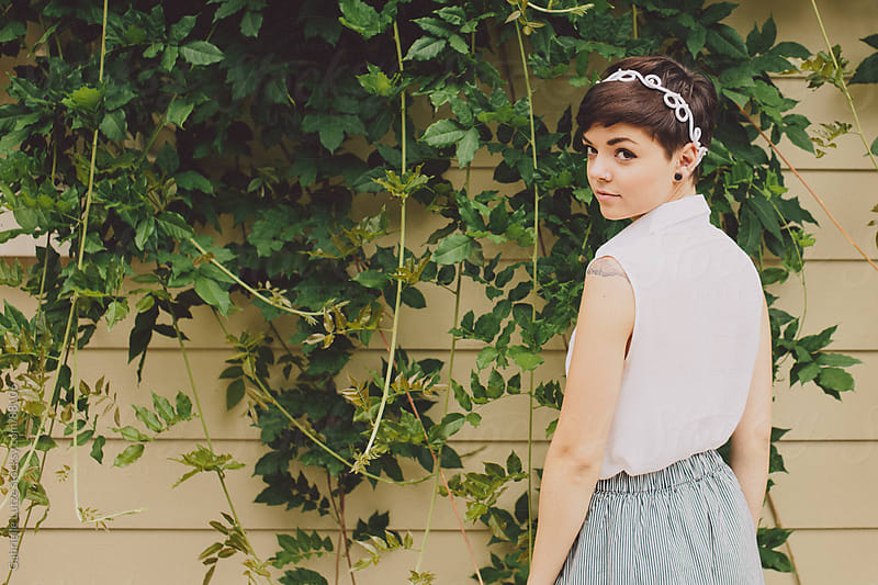 Girl with short hair in front of vines by Gabrielle Lutze for Stocksy United