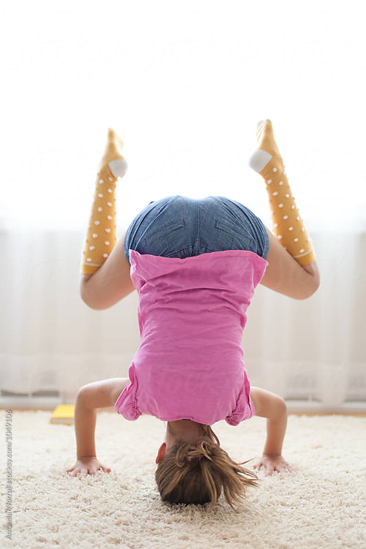 Tween girl practicing a yoga headstand by Amanda Worrall for Stocksy United