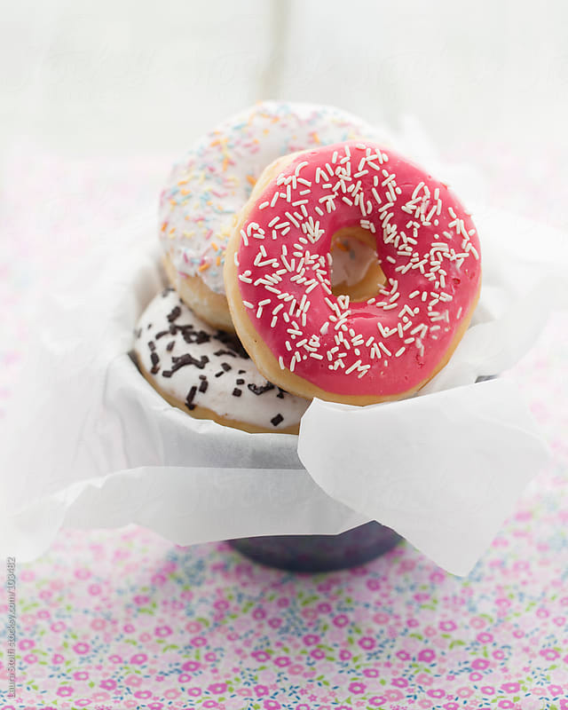 Colorful doughnuts with sugary on them in a cup on flowered cloth on wooden table by Laura Stolfi for Stocksy United