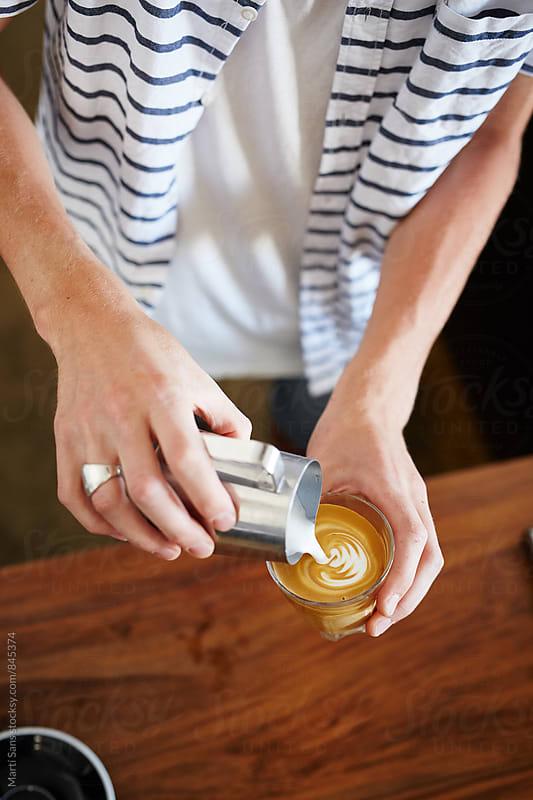 Bartender pouring steamed milk in latte by Martí Sans for Stocksy United