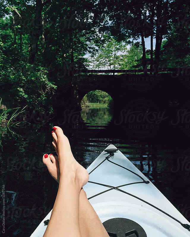 Woman's feet rest on a kayak  by Cara Dolan for Stocksy United