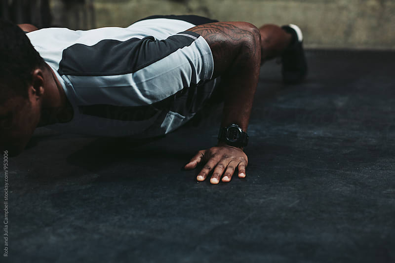 Young, fit black man training hard in fitness gym - pushups by Rob and Julia Campbell for Stocksy United