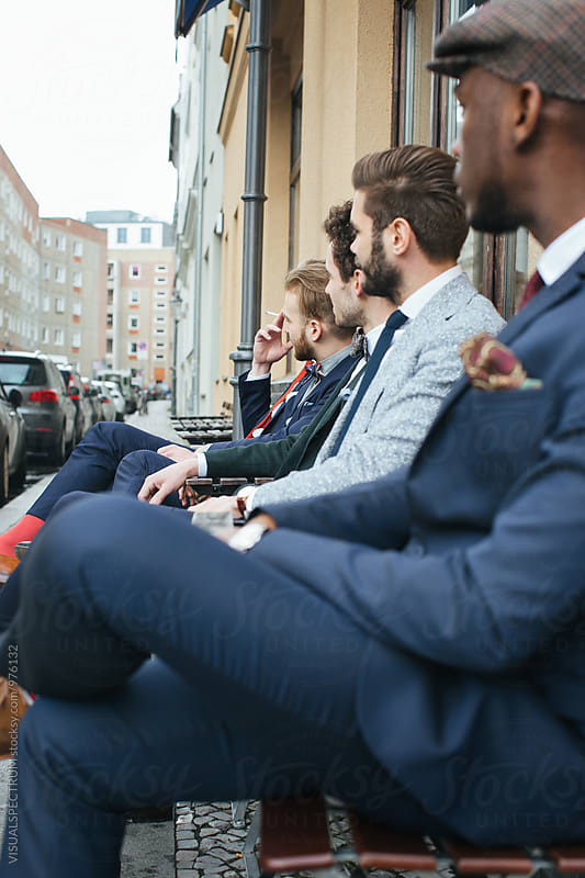 Five Stylish Young Men Sitting Outdoors and Looking Away by Julien L. Balmer for Stocksy United
