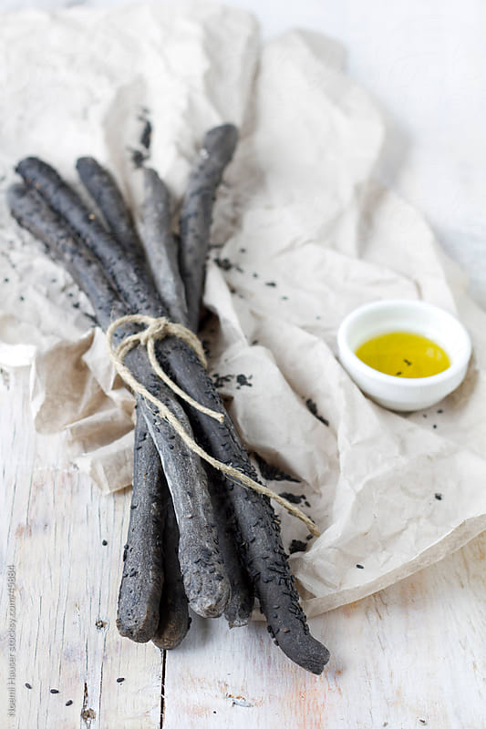 Squid ink coloured breadsticks with black sesame by Noemi Hauser for Stocksy United