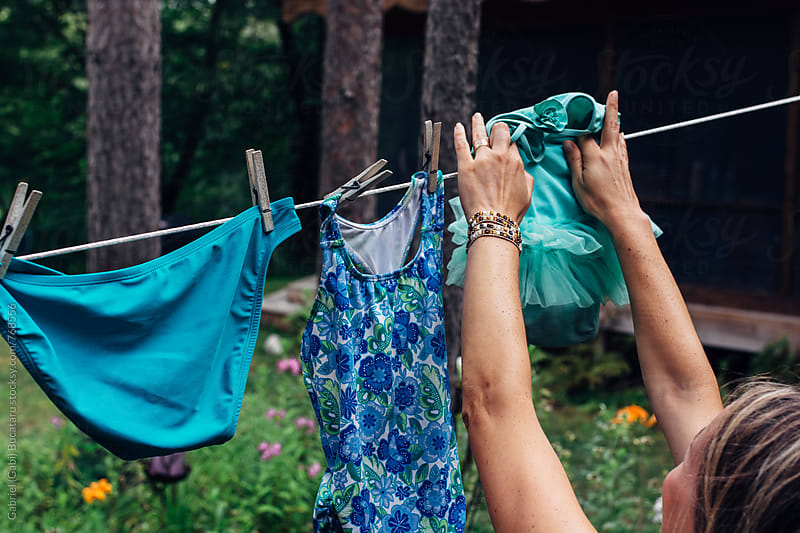 Woman hanging wet swimsuits out to dry by Gabriel (Gabi) Bucataru for Stocksy United