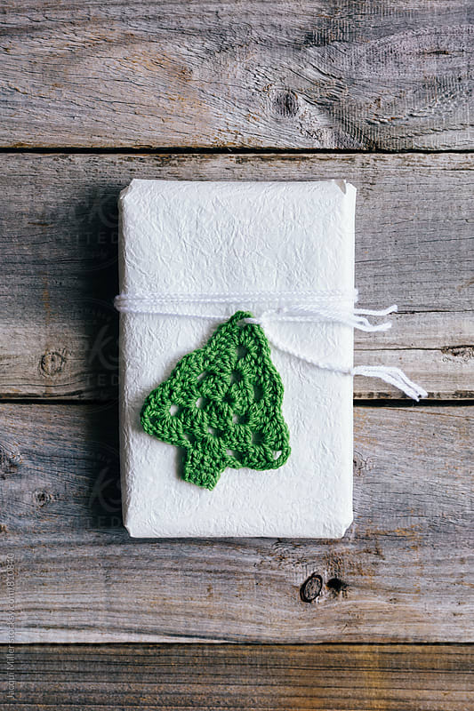 Simple Christmas gift tied with plaited wool, adorned with crocheted Christmas Tree by Jacqui Miller for Stocksy United