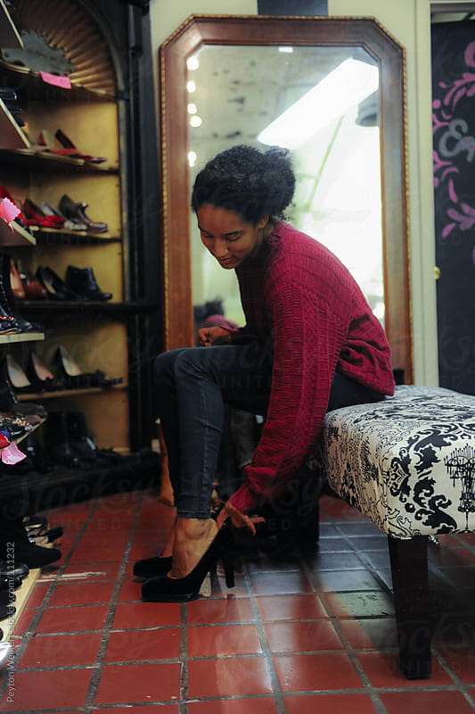 Young woman Sits Down In Store To Try On High Heels  by Peyton Weikert for Stocksy United
