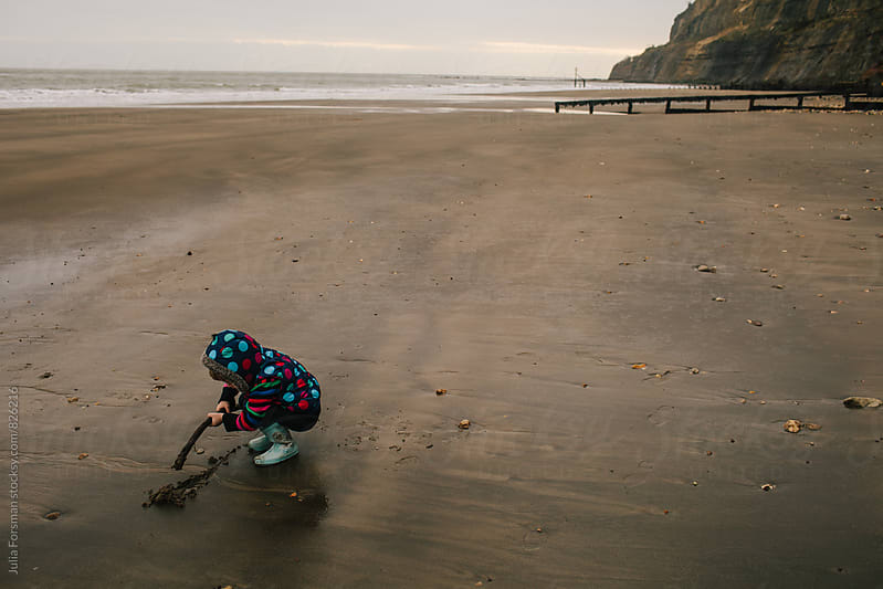 Little girl draws a line in the sand on an empty beach. by Julia Forsman for Stocksy United