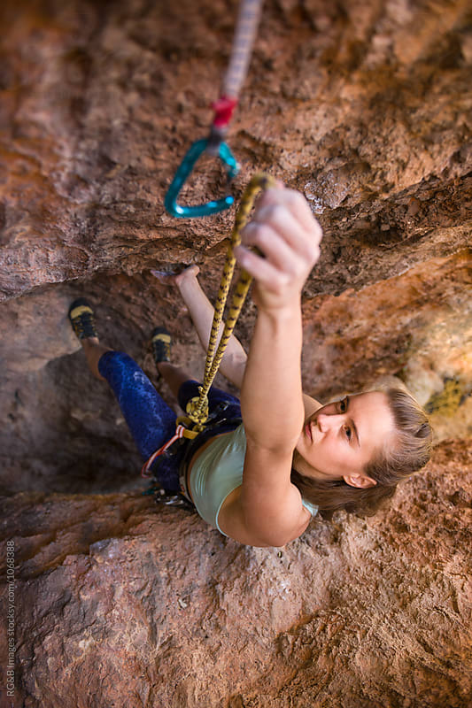 Rock climber clipping the rope in a quickdraw for safety by RG&B Images for Stocksy United