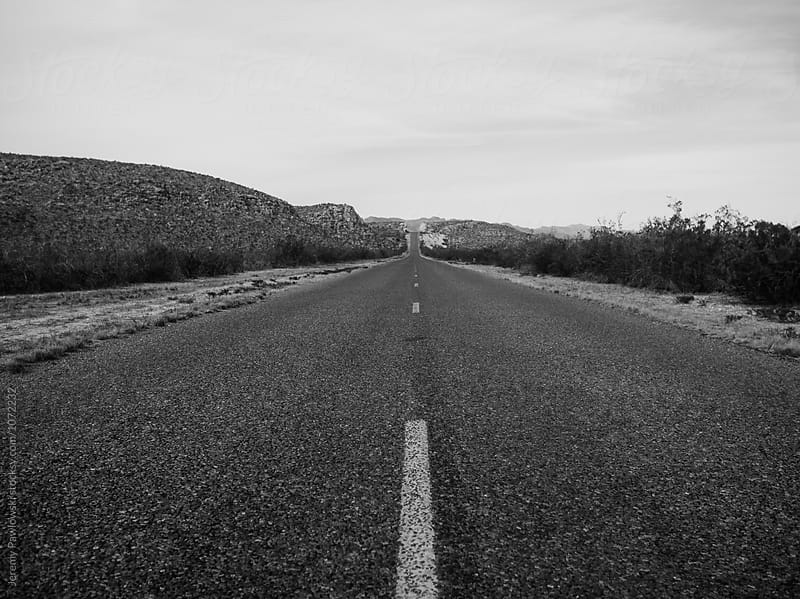 Moody black and white point of view shot of road running through desert in west Texas. by Jeremy Pawlowski for Stocksy United