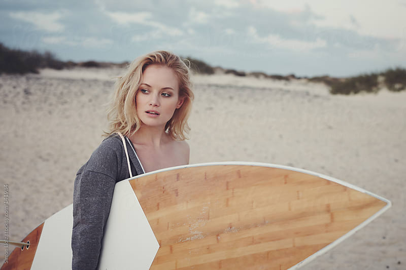 Surfer Girl holding board on empty beach by Simon Bolz for Stocksy United