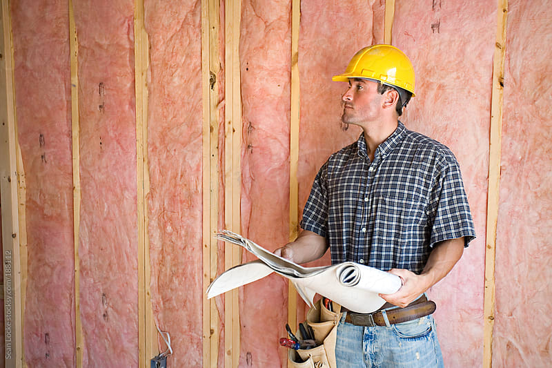 Construction: Builder Looks Up From Blueprints by Sean Locke for Stocksy United