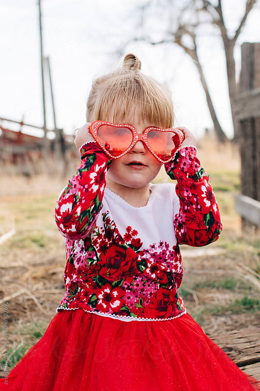 Toddler girl wearing heart sunglasses by Jessica Byrum for Stocksy United