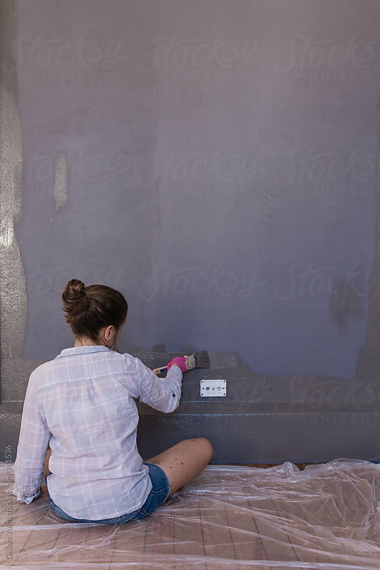 teen girl painting a grey wall by Gillian Vann for Stocksy United