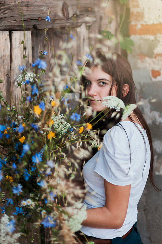Rural life: pretty woman with colourful wildflowers bouquet in front of wooden main door by Laura Stolfi for Stocksy United